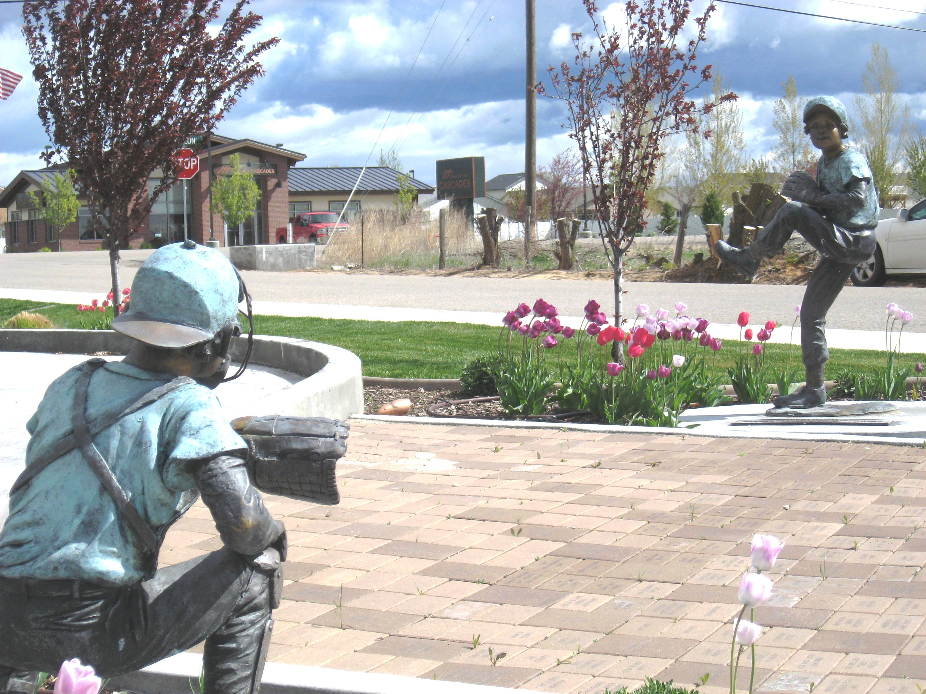 Statue of child pitching baseball to a catcher